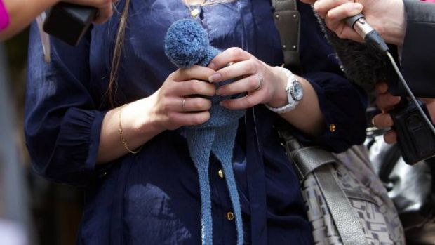 Sandra Bernobic holds her son's bonnet as she speaks to the media outside the inquest.