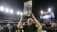 San Francisco Giants general manager Brian Sabean carries the World Series Trophy on the field after his team defeated ...