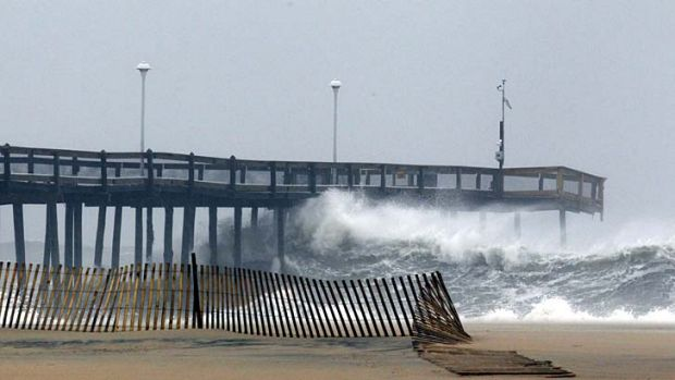 Bracing for trouble … waves crash into the pier in Ocean City, Maryland.