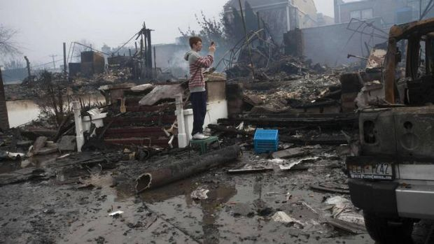 A resident looks over the remains of burned homes in the Rockaways section of New York.