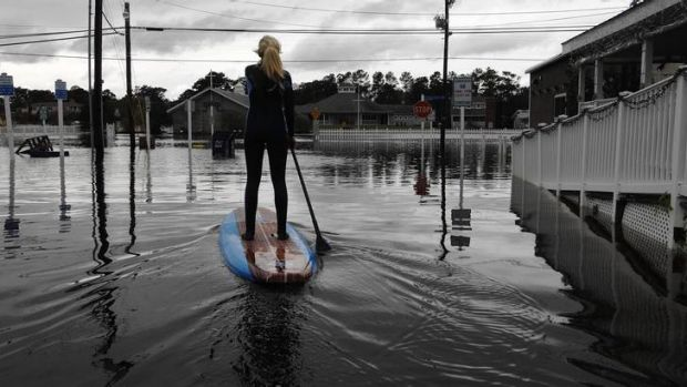 A woman paddle-boards down a flooded city street in the aftermath of Hurricane Sandy in Bethany Beach, Delaware.