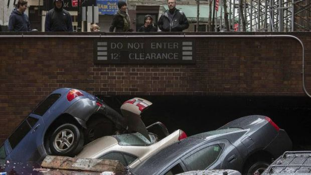 Residents stand over vehicles which were submerged in Lower Manhattan.