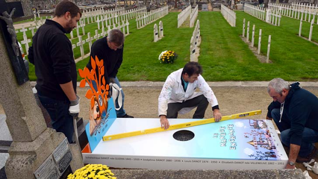 The future is here ... workers install an 'iron grave' at a cemetery in Nantes for TV show creator Serge Danot, who died ...