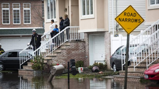 Nightmare ... Rescue workers check a flooded home for fuel leaks and other types of storm-related damage on Staten Island