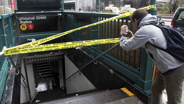 A man uses his smartphone to photograph a closed and flooded subway station in lower Manhattan.