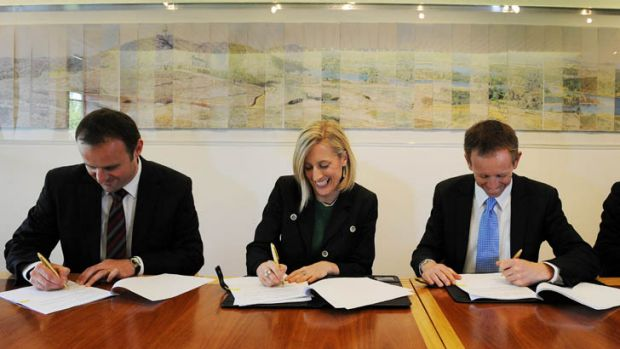 Gallagher signs the agreement with Rattenbury, right, and Deputy Chief Minister Andrew Barr, left.