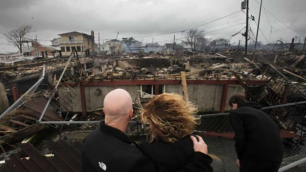 A couple survey the remains of the burnt-out home owned by her parents in Breezy Point, New York.