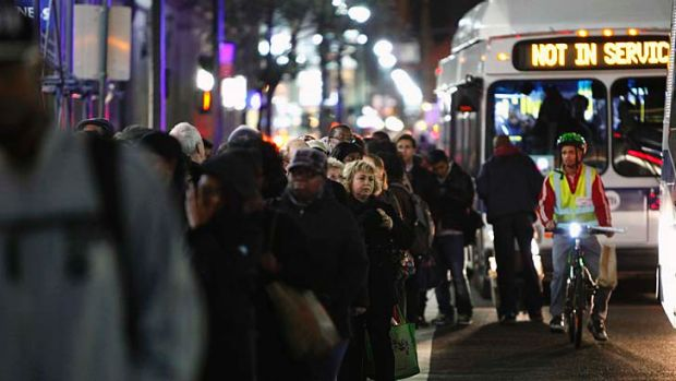 Residents line up for a bus in Manhattan.