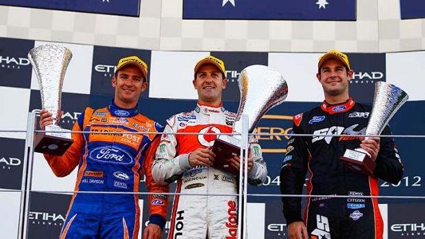 Jamie Whincup (centre) with second-placed Will Davison (left) and third-placed Shane Van Gisbergen on the podium in Abu ...