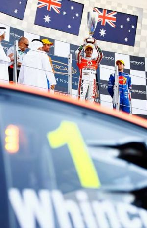 Jamie Whincup lifts the trophy after winning in Abu Dhabi.