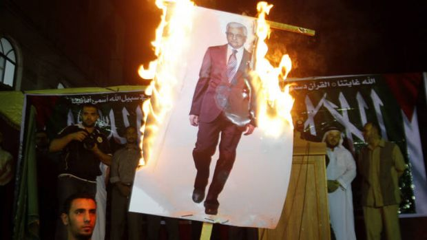 Anger ... Palestinians in the Jabaliya Refugee Camp, northern Gaza, burn a picture of Mahmoud Abbas in a protest against ...