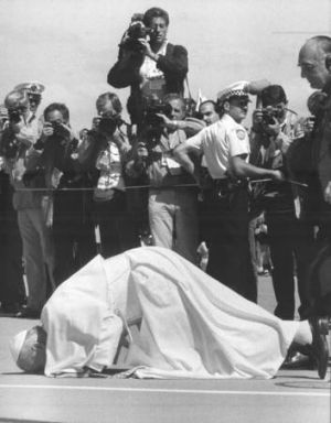 The Pope kisses the ground on his arrival.