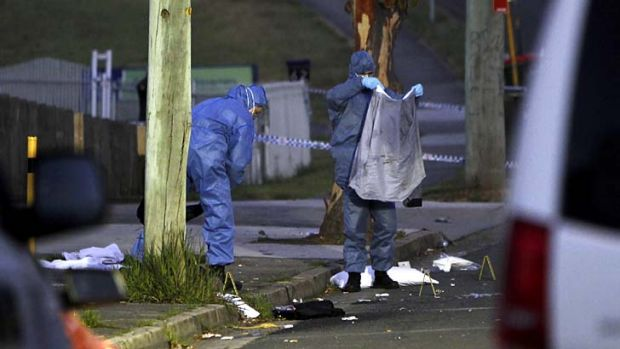 Police forensic officers examine the evidence after the triple shooting.