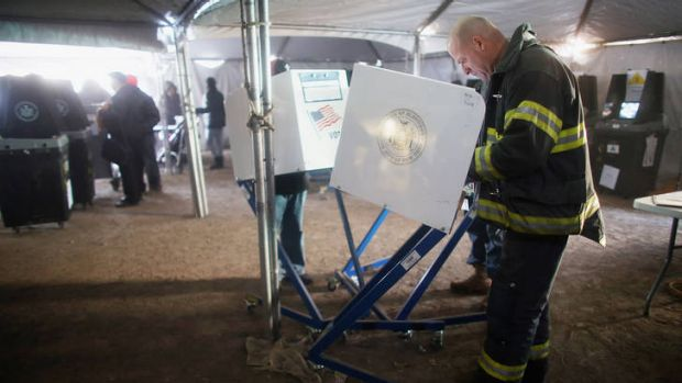 Vote goes on ... a Rockaway resident and New York City firefighter, Terence O'Donnell, marks his ballot in a makeshift ...