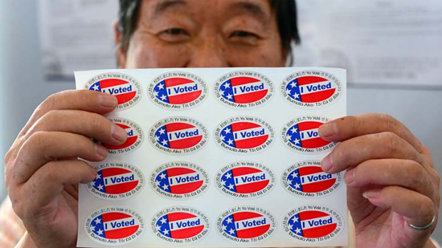 "Election official Henry Tung displays a sheet of ""I Voted"" stickers in Monterey Park, Los Angeles."