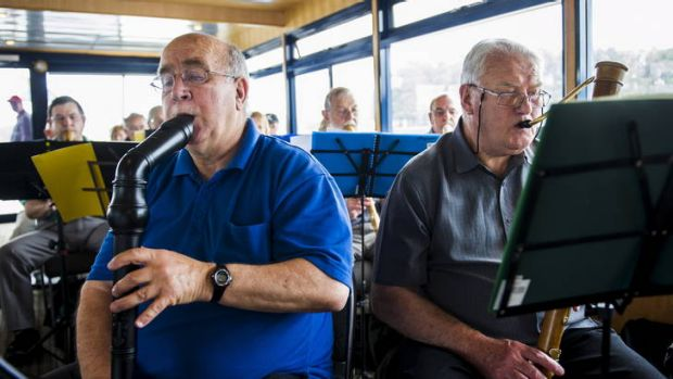 Mike Ilcher and Alan Brotherton, members of the Recorder Orchestra, play in the ferry on Lake Burley Griffin yesterday.  ...