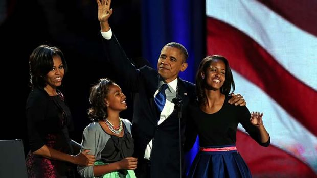 President Barack Obama walks on stage with first lady Michelle Obama and daughters Sasha and Malia to deliver his ...