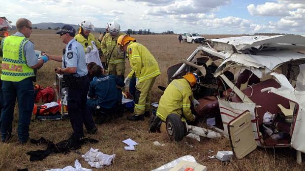 Emergency workers surround the wreckage of a plane that crashed at Beaudesert.