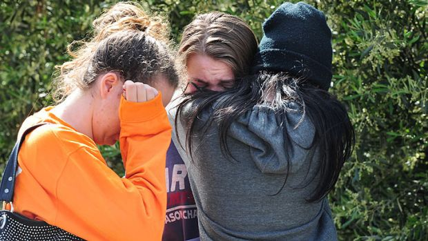 Young friends break down in tears at the crash scene, where three people died.
