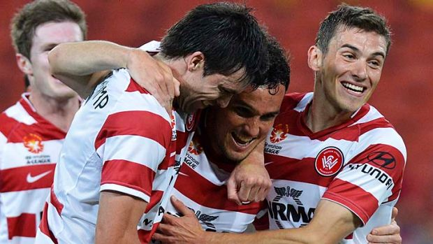 Mark Bridge of the Wanderers celebrates with team mates after scoring a goal during their A-League match against ...