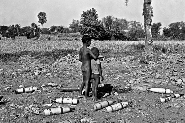 Two boys stand among rocket bombs left by the Pakistani army at the picnic corner in Jessore, Bangladesh. December 11, 1971.
