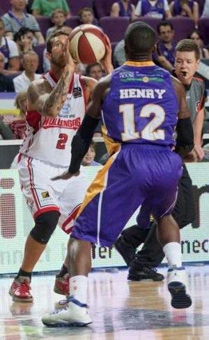 No right of way ... Sydney's Corin Henry tries to shut down a shot by Wollongong's Tyson Demos.