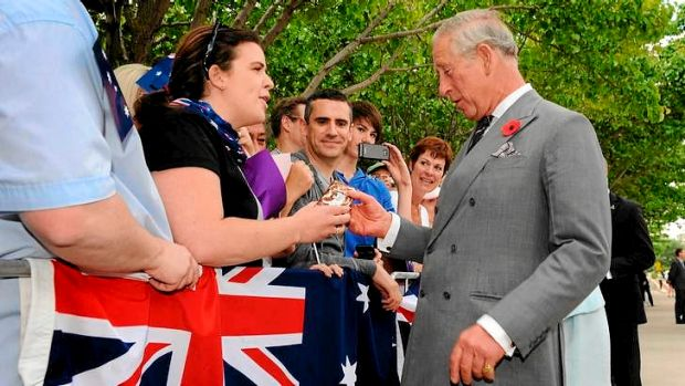 The Prince of Wales receives a packet of Tim Tams from a Allyson Richards.