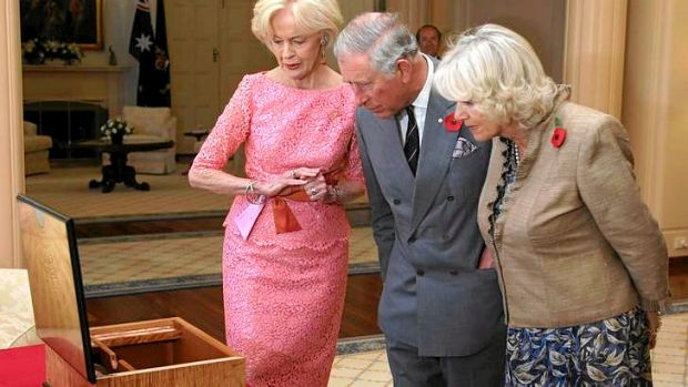 The Governor-General Quentin Bryce, Britain's Prince Charles and Camilla, Duchess of Cornwall inspect a gift, a writing ...