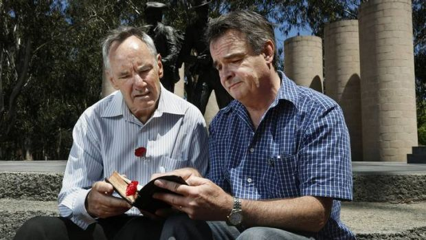 John Morgan and Darryl Johnston look at a bible that belonged to John's great uncle who was engaged to Darryl's great aunt.
