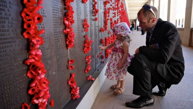 Arabella Bailey, 2, and her father, Afghanistan veteran Jamie Bailey, place a poppy on the Roll of Honour at the ...