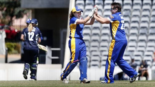 Victoria's Brianna Binch walks off the field as ACT Meteors wicket keeper Laura Wright and bowler Kris Britt celebrate ...