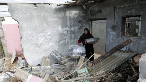 A Palestinian woman surveys the destruction to her house in Gaza following an Israeli airstrike.
