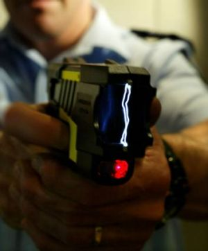 File photograph of police officer demonstrating the use of a Taser stun gun.