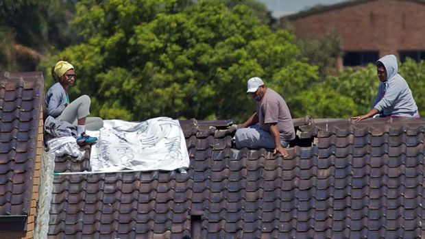 Three detainees on the roof at Villawood on Monday.