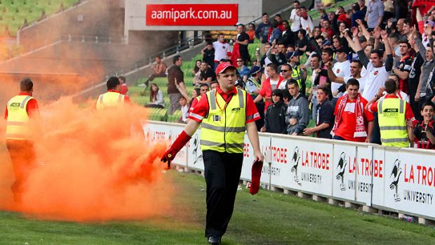 Terrible consequences...A match official carries away a flare thrown from the crowd at AAMI Park.