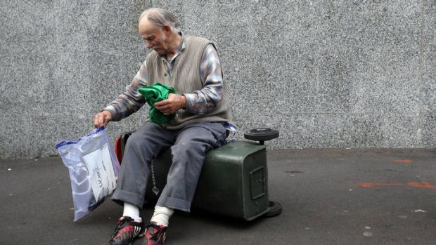 Sam Bracanov sits on a rubbish bin outside the Auckland District Court.