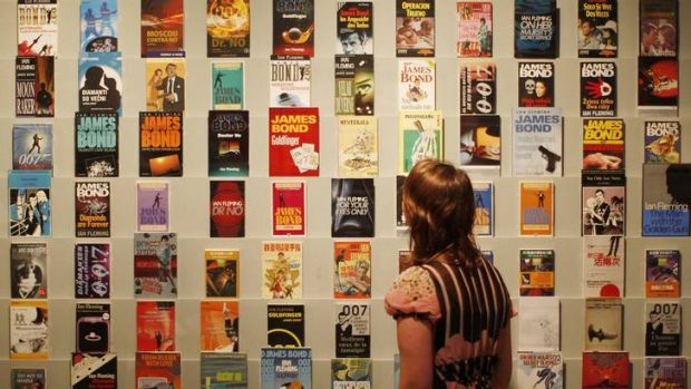 Spy who loves them ... a woman peruses a collection of original Bond novels at the <i>For Your Eyes Only</i> exhibition ...