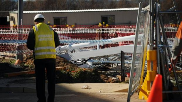 A Worksafe inspector looks at the site where a worker was killed in Kingston.