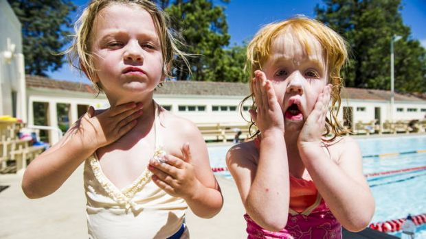 Penelope, 4, from Griffith, and Sage Haling  take a break from swimming to put on more sunscreen at Manuka Pool.