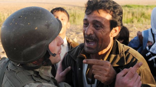 A Syrian man argues with a Turkish soldier while trying to cross the border during a bombardment that killed 18 people.