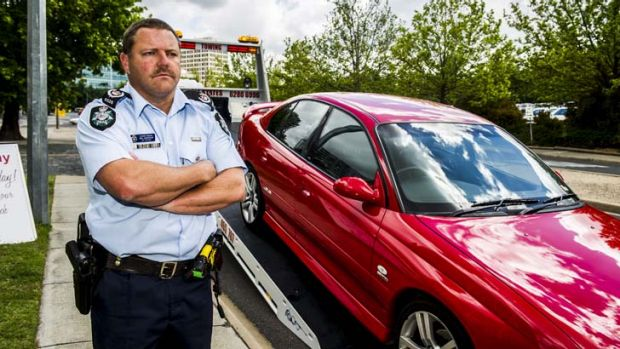 Sergeant Rod Anderson stands next to a tow truck as police warn that  they will seize vehicles from dangerous drivers at ...