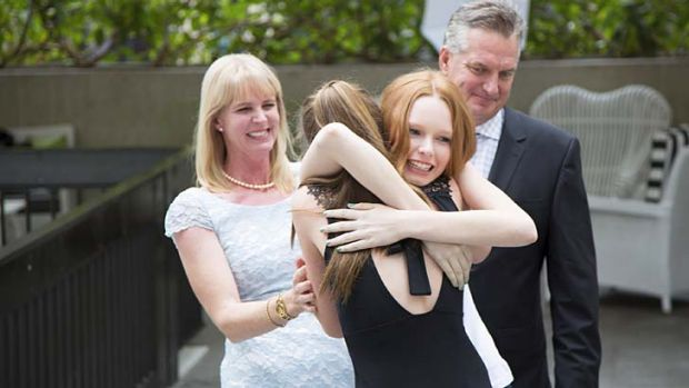 Dream comes true … Grace Simmons, centre, hugs her sister Annie as proud parents Blane and Adrienne look on.