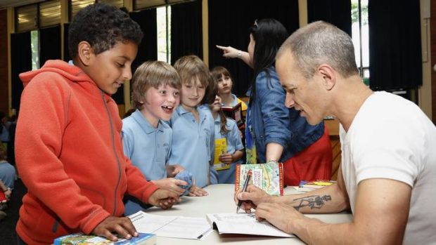 Ainslie School year 3 students Omar Algothmi, Benjamin Coram and Issac Jario get their books autographed by author Andy ...