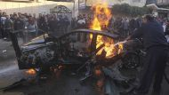 Palestinians help extinguish the fire after an Israeli air strike on the car of Hamas's top commander in Gaza City ...