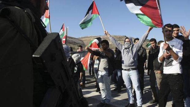 Tension ... protesters wave Palestinian flags in front of Israeli soldiers during a protest against Israel's military ...
