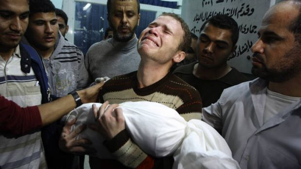 Grief ... the BBC journalist Jihad Misharawi weeps while he holds the body of his 11-month old son Ahmad.