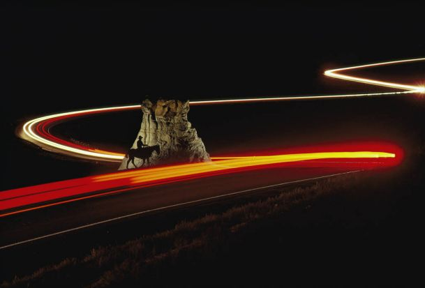 Time exposure of cars speeding past a cowboy on horseback, silhouetted against a rock formation. Argentina. Photo: Annie ...