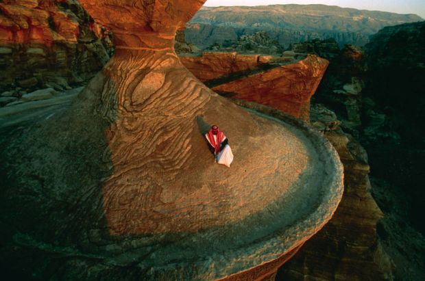 A Bedouin poses on the ruins of the ancient Jordanian city of Petra. Photo: Annie Griffiths Belt/National Geographic