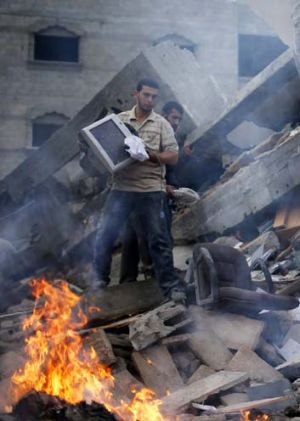 Palestinians remove items from the destroyed office building.