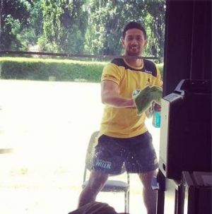 ACT Brumbies flyhalf Christian Lealiifano washes windows at the club's Griffith headquarters.